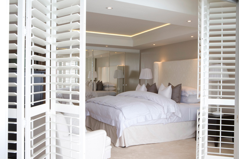 Open-plan full height shutters in bedroom